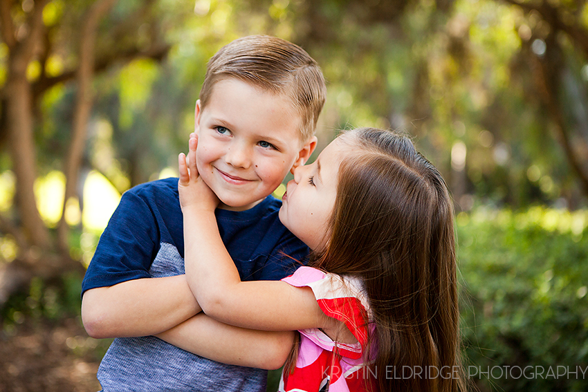 little girl kissing boy on the cheek