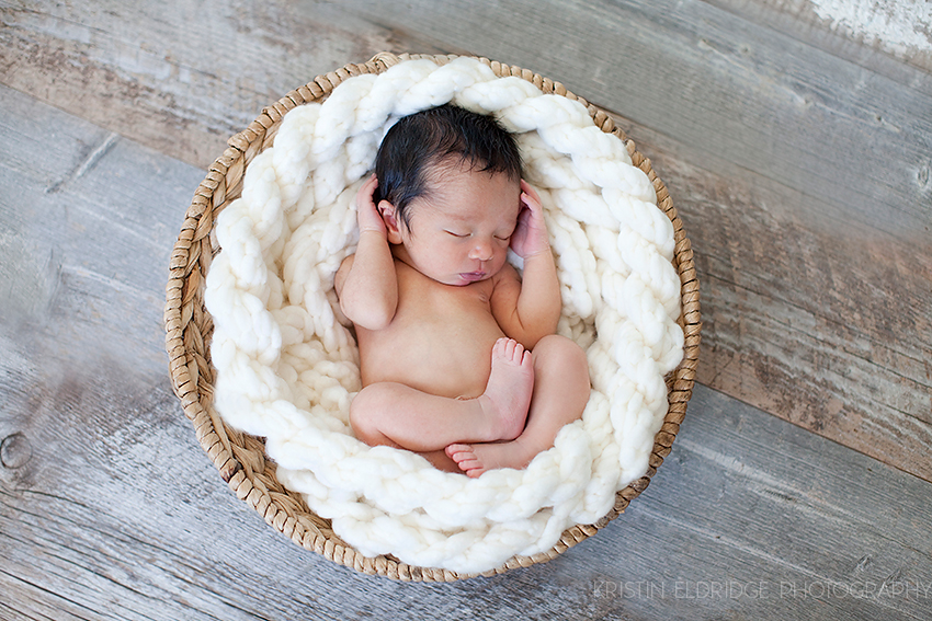 newborn in knitted yarn basket
