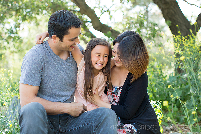 family laughing with their little girl